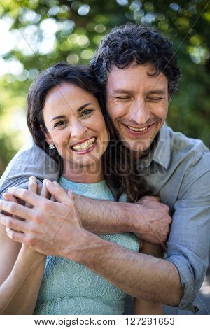 Portrait of smiling happy wife being hugged by husband at park