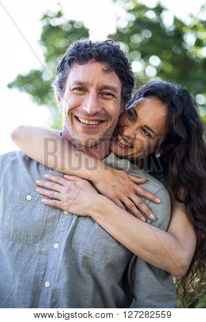 Portrait of smiling happy husband being hugged by wife at park