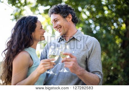 Smiling happy couple holding wineglasses in lawn