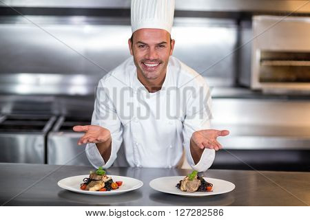 Portrait of smiling happy chef showing food plates in commercial kitchen
