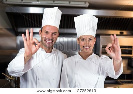 Portrait of smiling happy chefs showing ok signs in commercial kitchen