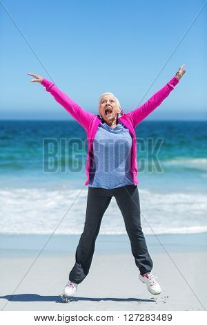 Happy mature woman outstretching her arms on the beach
