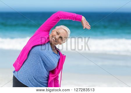 Thoughtful mature woman outstretching her arms on the beach