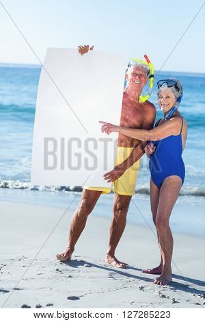Senior couple with beach equipment holding a white poster at the beach