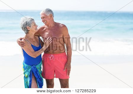 Cute mature couple looking at each other on the beach