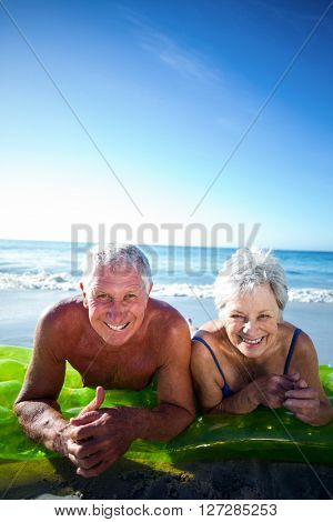 Senior couple lying on air mattress at the beach