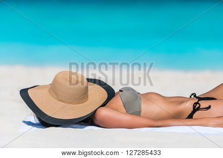 Beach relaxation woman sleeping sun tanning covering her face with straw hat for uv solar protection on caribbean destination blue ocean background. Vacation girl relaxing resting on summer travel.