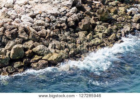 Surf crashing into stone sea wall on Curacao