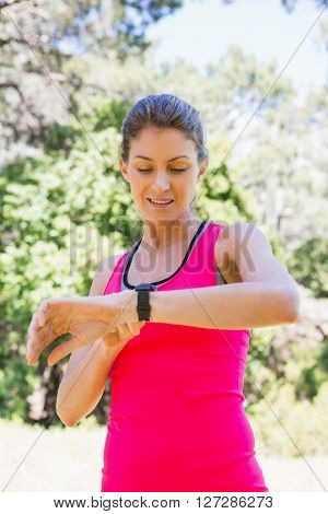 Woman looking at her watch after jogging