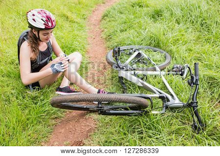 Woman hurting her leg after having an accident with the bike