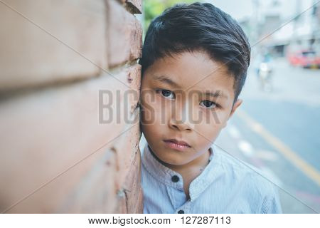 scared and alone, young Asian child who is at high risk of being bullied, abused, selective focus