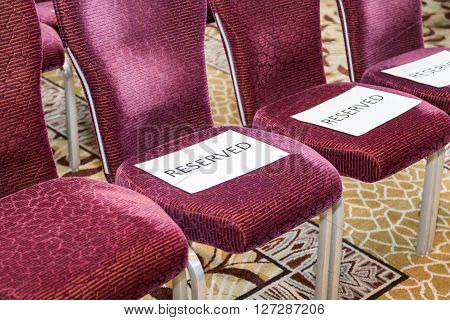 Red rows of chairs with white sheets reserved