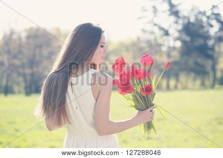 Beautiful long-haired romantic girl with a bouquet of tulips