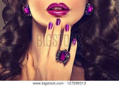 Beautiful girl model with curly hair showing purple manicure nails  and stylish jewelry  , ring and earrings .