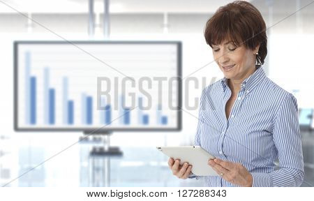 Senior casual caucasian female business executive looking at results on tablet at office with chart in background. Standing, copyspace.