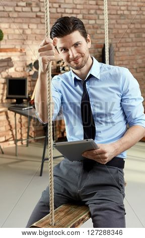 Handsome confident businessman sitting in swing, holding tablet, smiling.