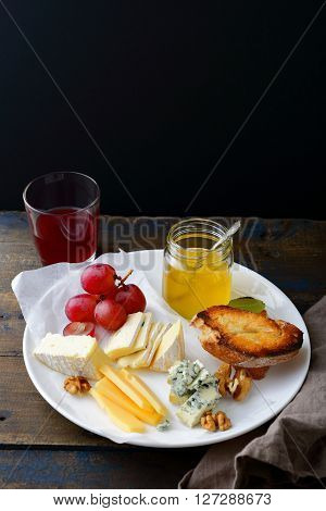 Assortment Of Sliced Cheeses With Grapes, Honey, Bread, Walnuts And Wine On Plate