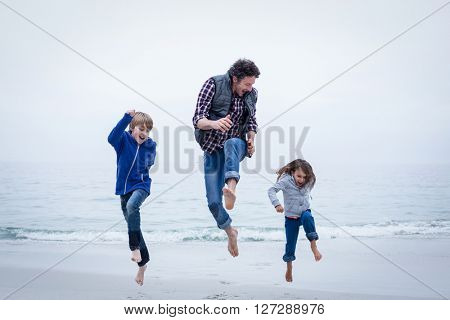 Full length of cheerful family jumping at sea shore against clear sky