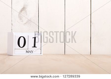 May 1st. Happy Labor Day. Image of may 01 white block calendar on white background with with ornamental plants in flowerpots. Spring day, empty space for text. International Workers' Day