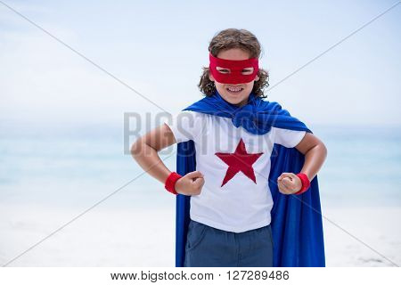 Portrait of boy in superhero costume with clenched fist at sea shore