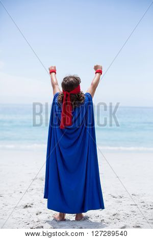 Rear view of boy in superhero costume with arms raised at beach