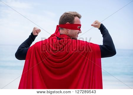 Rear view of man in superhero costume standing at sea shore