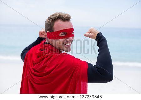 Portrait of happy man in superhero costume flexing muscles at sea shore