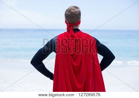 Rear view of superhero costume with hand on hip at sea shore against sky