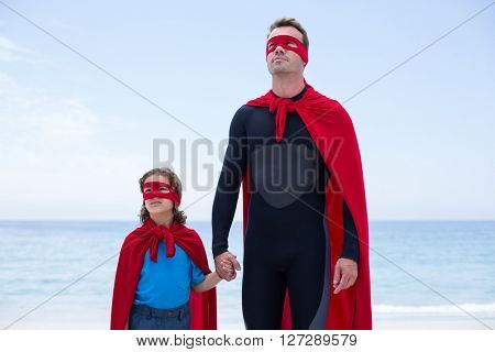 Father and daughter in superhero costume standing at sea shore against sky