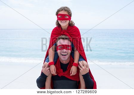 Portrait of cheerful father and son in superhero costume enjoying at beach