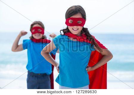 Portrait of happy siblings in superhero costume standing at sea shore