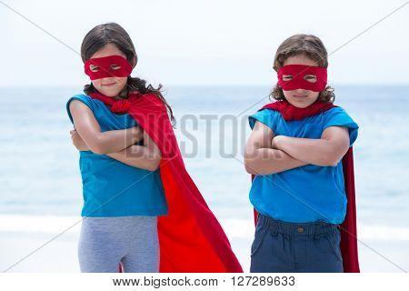 Sibling pretending to be superhero at sea shore