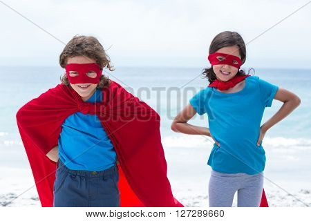 Happy siblings in superhero costume with hand on hip standing at beach