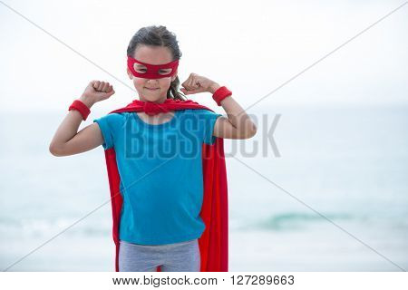 Portrait of girl wearing superhero costume flexing muscles at beach