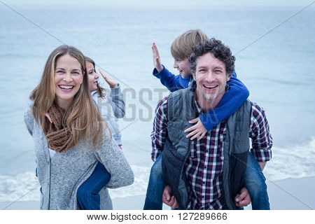 Happy parents carrying children on back at sea shore