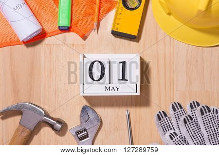 May 1st. Image of may 1 white blocks wooden calendar with construction tools on the table. International Workers' Day. Labour day concept.