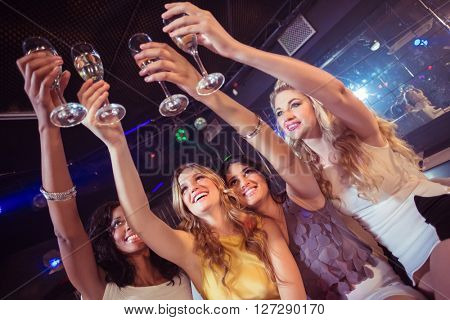 Pretty girls holding champagne glass in a nightclub