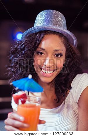 Pretty girl with cocktail and glitter hat in a club
