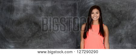 Happy young woman who is standing by a chalk board