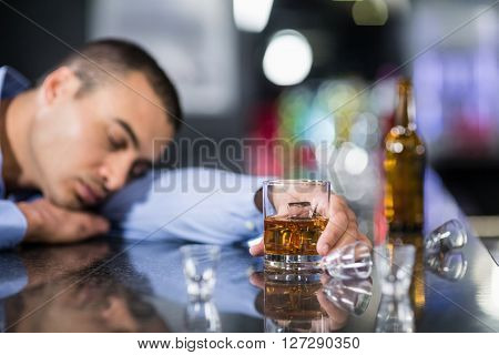 Tired man having a whiskey and sleeping on a counter in a pub