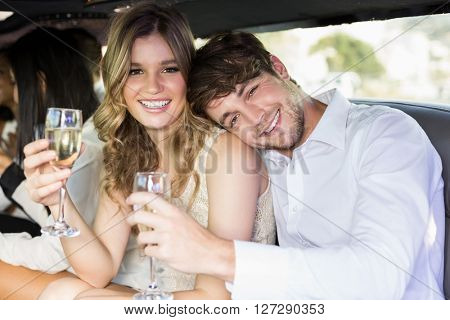 Well dressed couple drinking champagne in a limousine on a night out