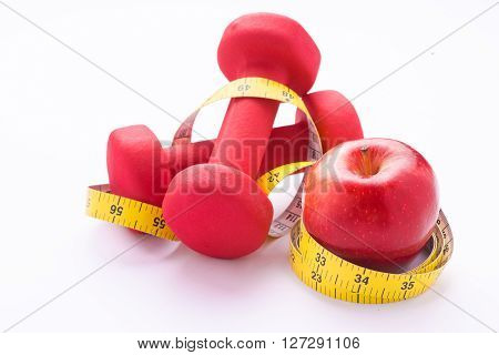 Measuring tape wrapped around a red apple and dumbbells as a symbol of diet.