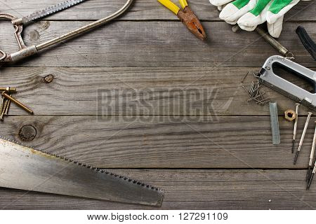 Set of old tools on a wooden table in the workshop with space for your text top view