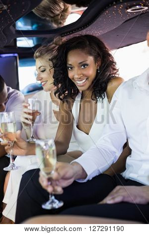 Well dressed woman drinking champagne in a limousine on a night out