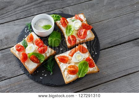Delicious and healthy food. Tomato and cheese bruschetta on a ceramic cutting board top view with copy space. Appetizer with wine
