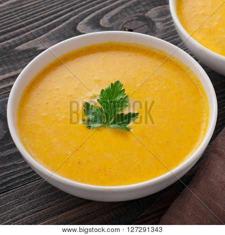 Two bowls of pumpkin soup with parsley leaf closeup
