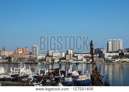 ships moored to the pier on the background of the city of Vladivostok