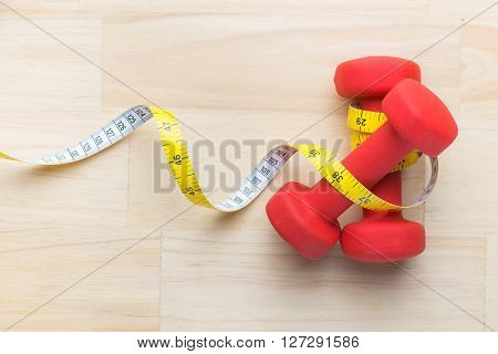 Measuring tape wrapped around a green apple and dumbbells as a symbol of diet