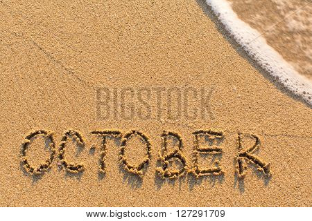 October - word drawn on the sand beach with the soft wave. Months series of 12 pictures.