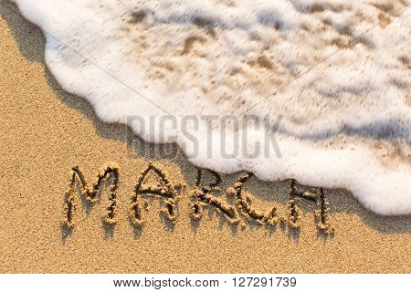 March - word drawn on the sand beach with the soft wave. Months series of 12 pictures.